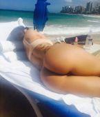 Morena en la playa con tatuaje