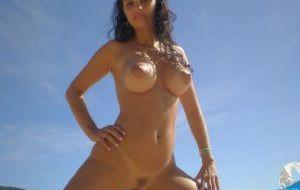 Morena latina desnuda en la playa